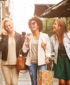 Three women walking outdoors with shopping bags