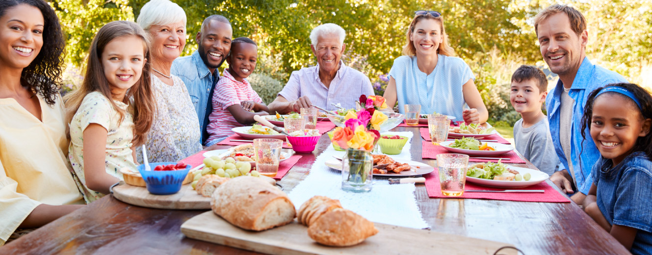 A diverse family sitting outdoors at picnic table